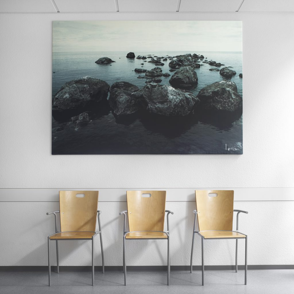 Stühle im Wartezimmer mit beruhigendem Bild von Felsen im Wasser.